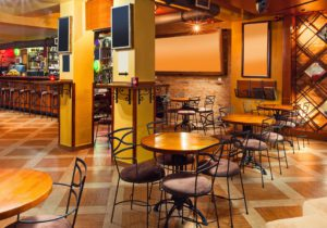 Interior of a modern pub in orange and wooden colors.